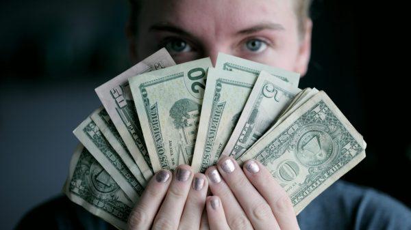 women holding U.S dollar banknotes